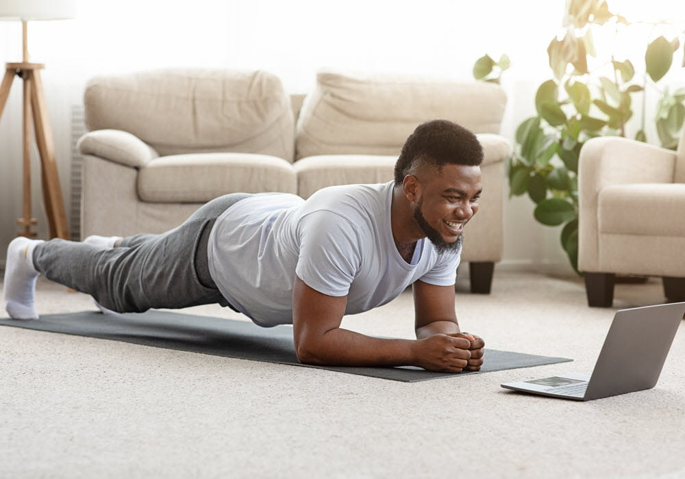 Man exercising at home with a laptop