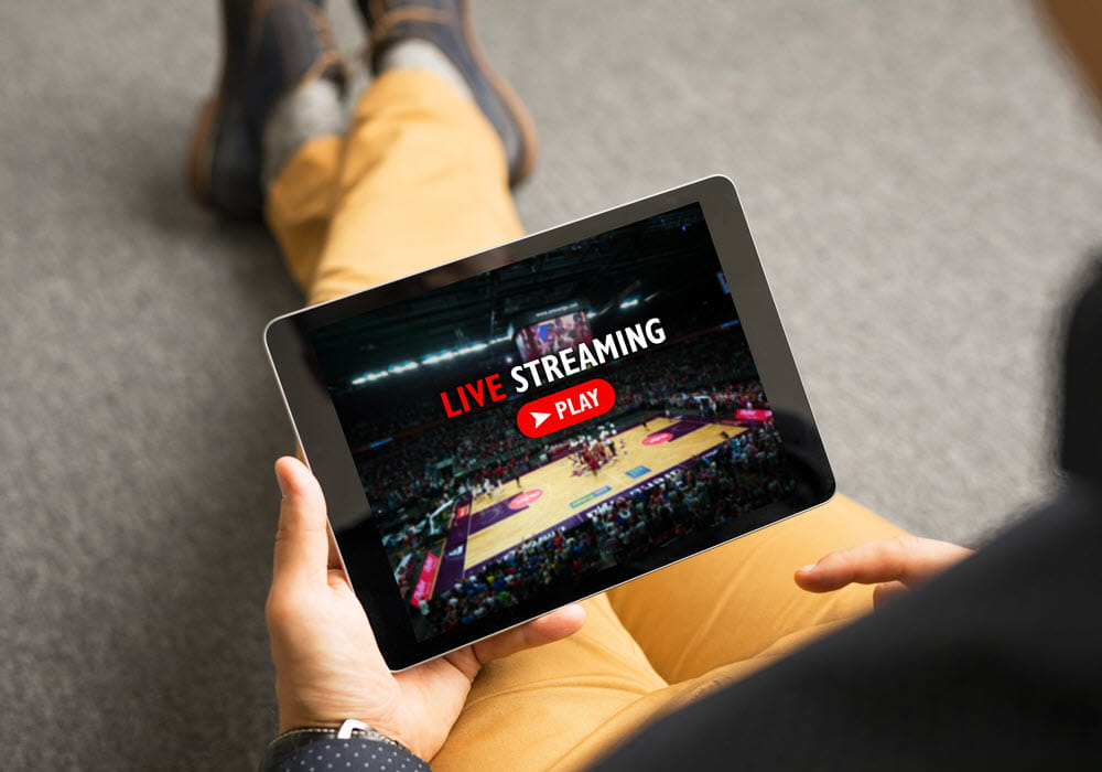 Man watching sports live streaming using online service